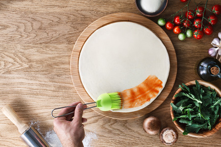 pizza base: Pizza cooking process: spreading tomato sauce on pizza base with a silicone pastry brush. Wooden background, top view.