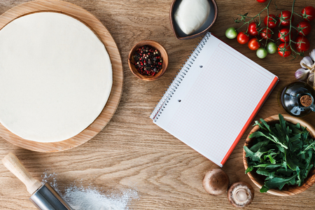 pizza base: Copybook surrounded by pizza base  and ingredients on a wooden textured table. Top view. Stock Photo