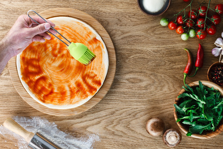 pizza base: Pizza cooking process: spreading tomato sauce on a pizza base with a silicone pastry brush. Wooden background, top view.