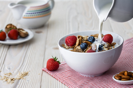 milk jugs: Pouring milk into the bowl with multigrain natural flakes with blueberries and raspberries Stock Photo
