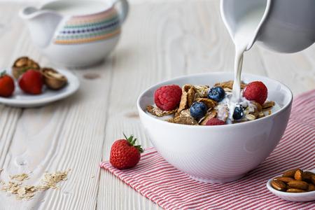 mleko: Wylewanie mleka do miski z wieloziarnistego naturalnych płatków z jagodami i malinami