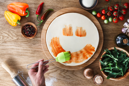 Funny pizza cooking: drawing smile with a tomato sauce.