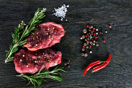 animal blood: Two beef steaks garnished with a couple of rosemary twigs, dwarf chili peppers, sea salt granules and peppercorns on dark background. Top view.