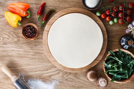 masa: Base de pizza de masa fresca y los ingredientes en una mesa de madera con textura. Vista superior.