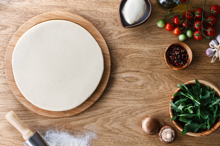 dough: Base de pizza de masa fresca y los ingredientes en una mesa de madera con textura. Vista superior.