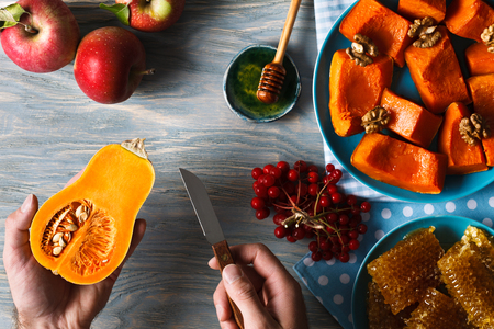 Autumn menu. Man hands holding little pumpkin and a knife against the background of fresh apples, a bunch of viburnum berries, honeycombs and a dish of roasted pumpkin with walnuts.