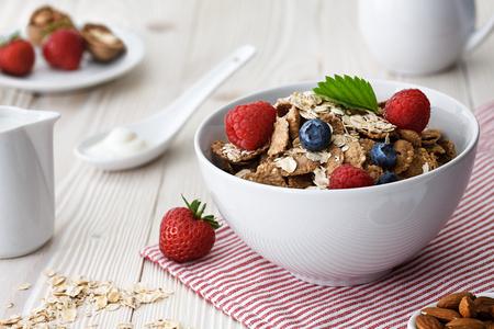 Healthy breakfast with multigrain natural flakes , raspberries, blueberries and almonds.