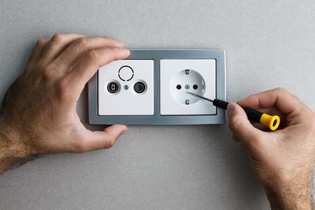 mantenimiento: La instalación de una toma de corriente de plata montado en la pared de CA con un destornillador en una pared gris, la renovación de su casa. Cierre de vista. Foto de archivo