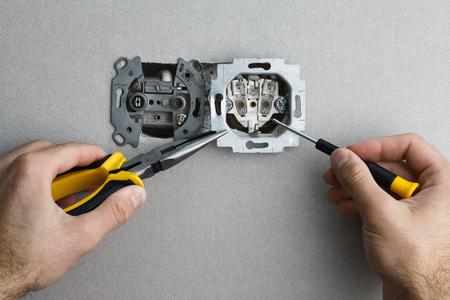 Het installeren van een muur gemonteerde AC stopcontact met een schroevendraaier op een grijze muur, de renovatie van huis. Close-up bekijken.