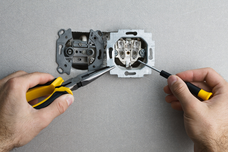ac: Installing a wall-mounted AC power socket with a screwdriver on a grey wall, renovating home. Close up view. Stock Photo
