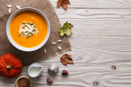 little table: Traditional pumpkin soup with seeds and ingredients still life.