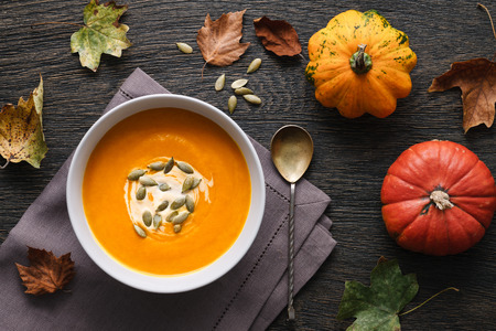Traditional pumpkin soup on a dark wooden background with autumn leaves and decorative pumpkins.