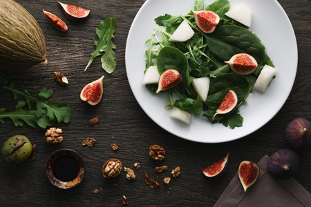 A salad with green leaves of rocket and spinach, fig pieces and melon in a white plate on dark wooden background. Top view.