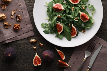 A salad with green leaves of rocket and spinach, fig pieces and walnuts in a white plate on dark wooden background. Top view.