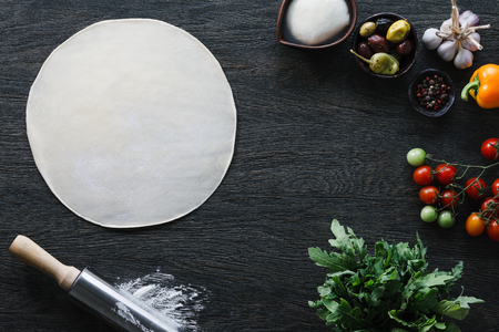 Italian pizza cooking process. Pizza dough and the ingredients: mozarella cheese, olives, pepper, garlic, tomato, rocket salad and spicies. Standard-Bild
