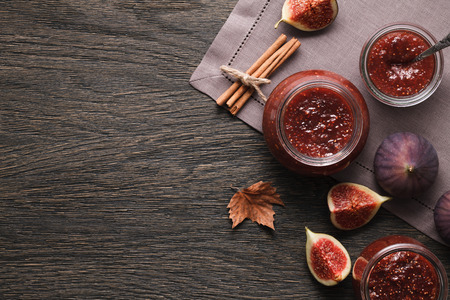 Glass jars full of fig jam and fig fruits on a dark wooden background