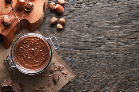 A food background of a hazelnut spread glass jar, milk chocolate and hazelnuts. Top view.
