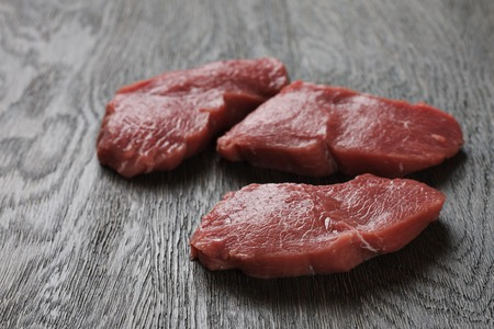 animal blood: Three raw beef steaks on a dark wooden board. Close up view. Stock Photo