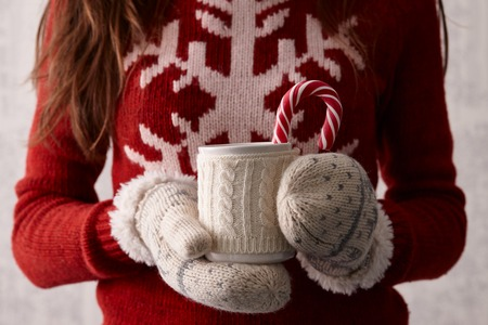 Woman hands in cute christmas mittens holding a cup of coffee or cocoa with a candy cane Stock Photo