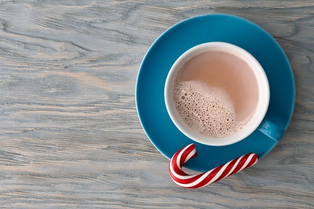 cioccolato natale: A big cup of cocoa with a red striped candy cane on a blue wooden background, top view. Archivio Fotografico