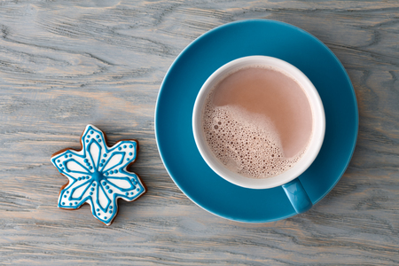 A big cup of cocoa with a gingerbread snowflake-shaped candy on a blue wooden background, top view. Standard-Bild