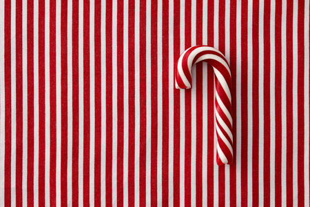 peppermint candy: Striped peppermint candy cane on a striped textile background Stock Photo