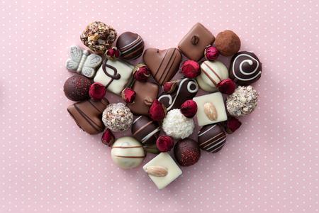Chocolade snoepjes en droog nam bloemen hartvorm samenstelling. Zoete gift van liefde voor St. Valentijnsdag. Stockfoto