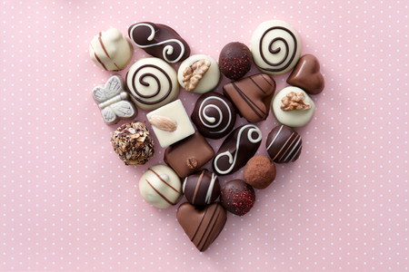 st  valentine: Chocolate candies heart shape composition. Sweet gift of love for St. Valentines Day. Stock Photo