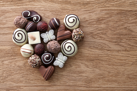 Chocolate candies heart shape composition on a wooden background. Sweet gift of love for St. Valentines Day.