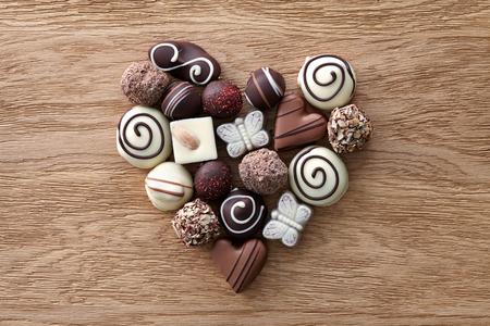 Chocolade snoepjes hart vorm samenstelling op een houten achtergrond. Zoete gift van liefde voor St. Valentijnsdag. Stockfoto