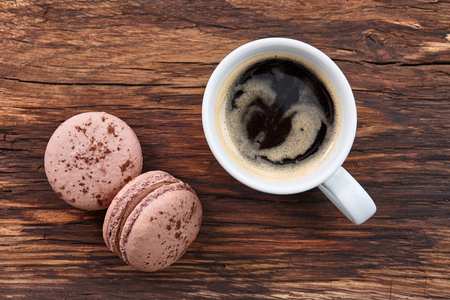 americano: A cup of morning americano coffee with chocolate french macarons on a vintage wooden background Stock Photo