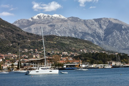 contradiction: Sunny marine lanscape with yacht and mountain Lovcen snowy peak.