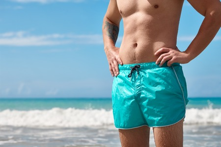 Caribbean vacation travel. Athletic man body and swimshorts close up on a sea shore background. Stock Photo