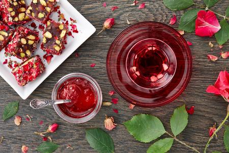 Een glas Turkse kopje hibiscus thee met stukjes fruit, rose jam en Turkish Delight met rozenblaadjes op een donkere houten achtergrond. Bovenaanzicht.