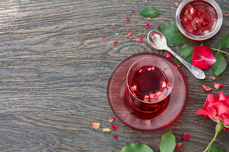 Food background with a glass turkish cup of hibiscus tea with fruit pieces, rose jam and rose flower on a dark wooden background. Stock Photo