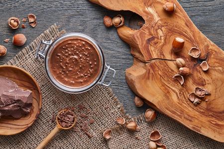 cobnut: Glass jar of hazelnut spread with nuts pieces on dark wooden background Stock Photo
