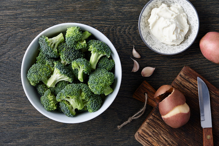 brocoli: A bowl with fresh broccoli, cloves of garlic, potatoes and cream cheese on dark wooden background. Brocoli soup ingredients. Stock Photo