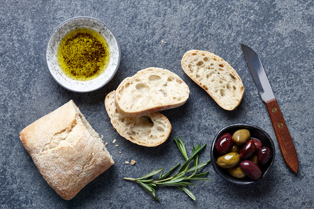 extra virgin: Sliced Italian ciabatta bread with extra virgin olive oil, olives and rosemary on gray stone background