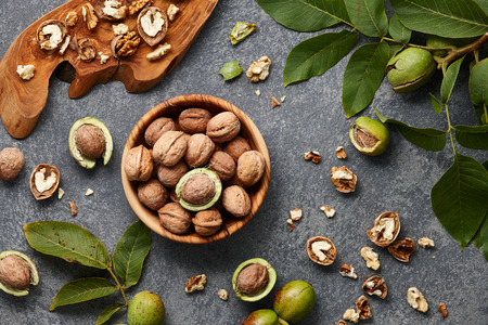 Wooden bowl with fresh walnuts, leaves and nut shell on gray stone background. Autumn seasonal.