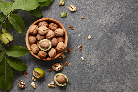 nut shell: Wooden bowl with fresh walnuts, leaves and nut shell on gray stone background. Autumn seasonal.