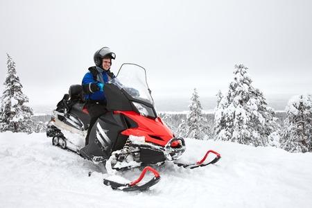 Happy smiling man driving snowmobile in Finnish Lapland Standard-Bild