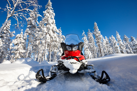 Red snowmobile in Finnish Lapland sunny landscape