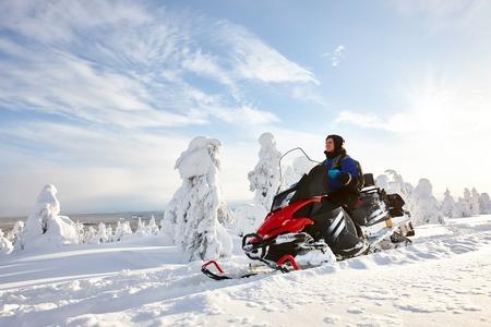 Man rijden sneeuwscooter in snowyfield in een zonnige dag. Lapland, Finland. Stockfoto