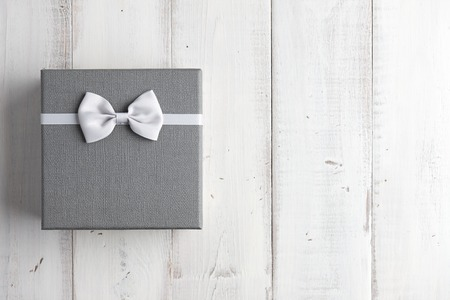 restrained: Strict gray gift box with white bow on wooden background