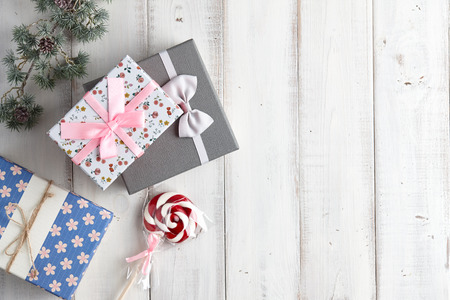 fur tree: Christmas gift boxes and lollypop under fur tree branch on white wooden background