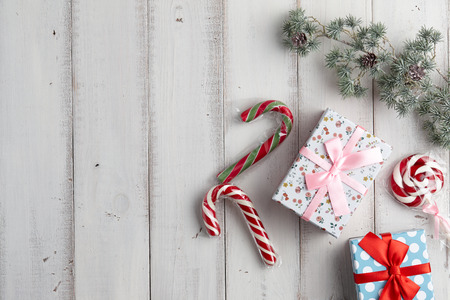 fur tree: Christmas gift boxes with lollypop and candy canes under fur tree branch on white wooden background