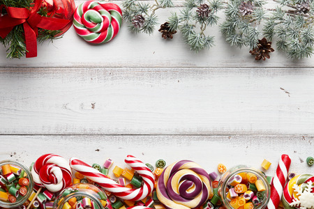 fur tree: Christmas background with colorful lollipops mix, fur tree and jingle bells