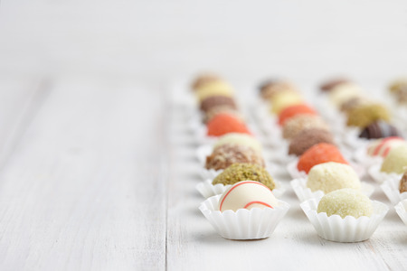 bonbons: Chocolate truffle candies on white wooden background