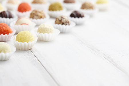 truffe blanche: Chocolate truffle candies on white wooden background