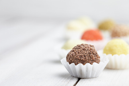 Chocolate truffle candies on white wooden background